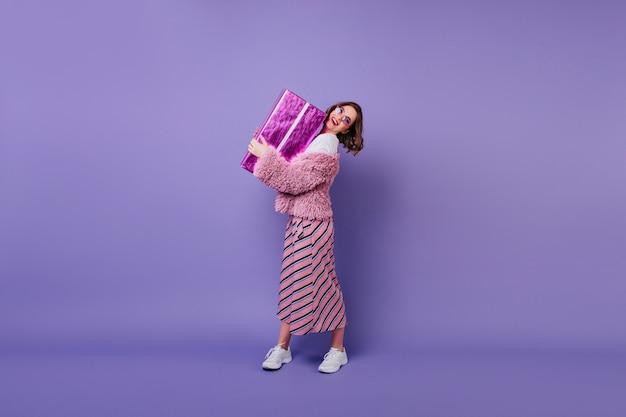Pełnometrażowy Portret Zadowolony Kaukaski Kobieta W Trampkach Trzymając Pudełko Na Prezent. Kryty Strzał Eleganckiej Modelki Stwarzających Z Prezentem Urodzinowym I Uśmiechnięty. Darmowe Zdjęcia