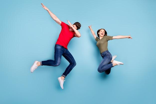 Pełnowymiarowe Zdjęcie Funky Szalonych Dwoje żonatych Studentów Zabawa Skakanie Mężczyzna Wykonuje Tancerze Dab Kobieta Podnosi Ręce Nosić Zielony Czerwony T-shirt Dżinsy Dżinsy Trampki Na Białym Tle Niebieski Kolor Tło Premium Zdjęcia