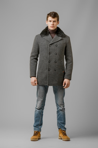 Pełny długość portret przystojny mężczyzna w ciepłym żakiecie pozuje w studiu Premium Zdjęcia