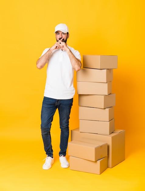 Pełny strzał doręczeniowy mężczyzna wśród pudeł nad odosobnionym kolorem żółtym pokazuje znak cisza gest Premium Zdjęcia