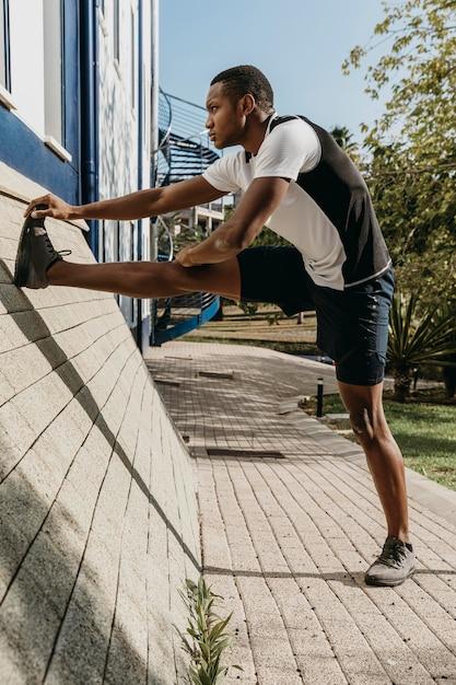 Pełny Strzał Mężczyzna Rozciągający Nogę Premium Zdjęcia