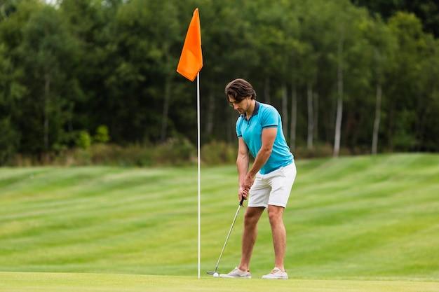Pełny strzał pasuje dorosłego człowieka gry w golfa Darmowe Zdjęcia