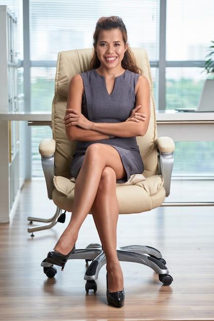 Pełny strzał ufnej damy siedząca noga nad nogą w biurowym krześle z rękami składać Darmowe Zdjęcia