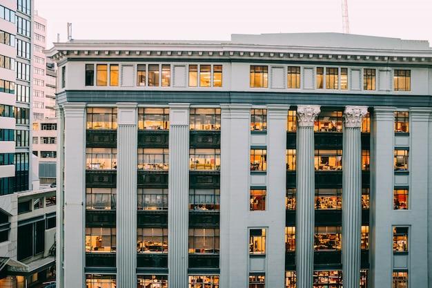 Pełny Widok Nowoczesnego Białego Budynku Z Kolumnami I Rycinami Na Nich Z Oknami I światłami Darmowe Zdjęcia
