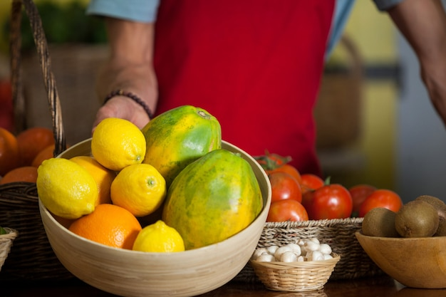 Personel Trzymający Miskę Owoców Przy Ladzie Na Rynku Premium Zdjęcia