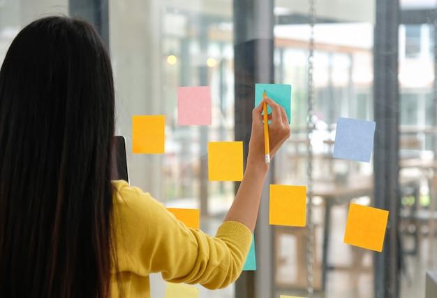 Personel żeński Używa Pióra Do Pisania Papernotu Na Szkle, Aby Zaplanować Swoją Pracę. Premium Zdjęcia