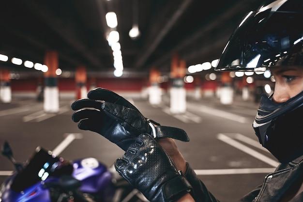 Pewna Siebie Młoda Zawodniczka Ubrana W Stylowy Kask Motocyklowy, Zakładająca Skórzane Rękawiczki, Pozuje Odizolowany Na Podziemnym Parkingu Ze Swoim Niebieskim Motocyklem. Selektywne Skupienie Się Na Kobiecych Rękach Darmowe Zdjęcia