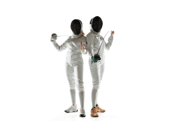 Pewność Siebie. Nastoletnie Dziewczyny W Strojach Szermierki Z Mieczami W Rękach Na Białym Tle. Młode Modelki ćwiczą I Trenują W Ruchu, Akcji. Copyspace. Darmowe Zdjęcia