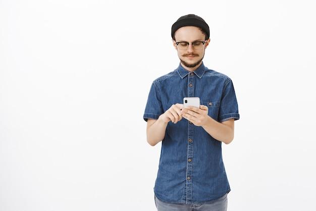 Pewny Siebie, Inteligentny I Kreatywny Menadżer Męskiego Studia W Czapce I Okularach Z Brodą, Piszący Wiadomość W Smartfonie Lub Szukający Informacji W Internecie, Wpatrując Się W Ekran Gadżetu Zrelaksowany Na Szarej ścianie Darmowe Zdjęcia