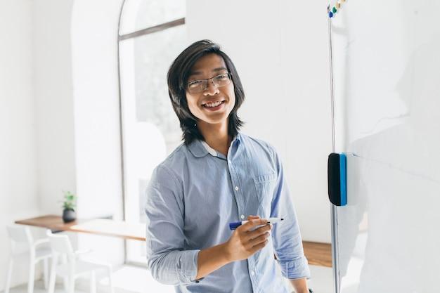 Pewny Siebie Japoński Student W Modnych Okularach Trzymając Marker, Stojący W Pobliżu Tablicy Darmowe Zdjęcia
