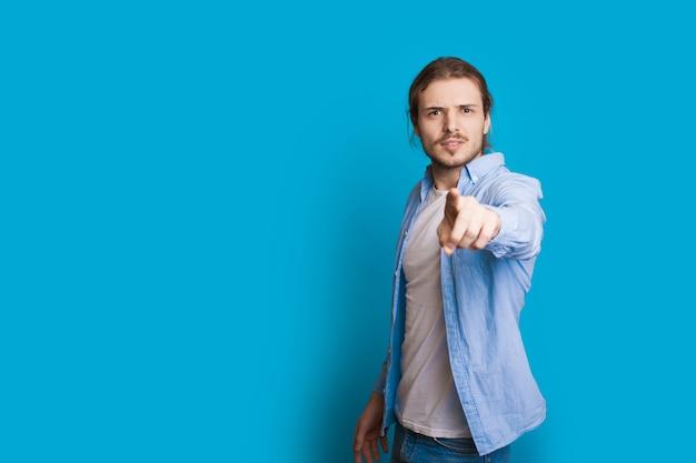 Pewny Siebie Kaukaski Mężczyzna Z Długimi Włosami I Brodą, Wskazując Na Niebieską ścianę Z Wolną Przestrzenią Premium Zdjęcia