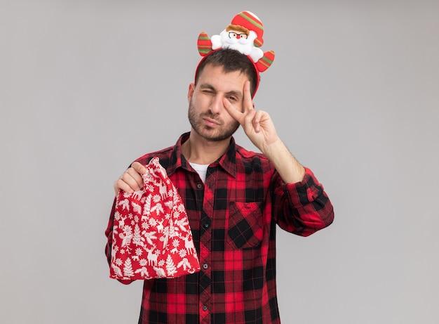 Pewny Siebie Młody Kaukaski Mężczyzna Ubrany W świąteczną Opaskę Trzymającą świąteczny Worek Patrząc Na Kamerę Pokazującą Symbol V W Pobliżu Oka Mrugającego Na Białym Tle Na Białym Tle Z Miejsca Na Kopię Darmowe Zdjęcia