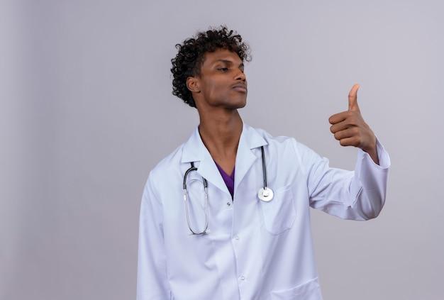 Pewny Siebie Młody Przystojny Ciemnoskóry Lekarz Z Kręconymi Włosami W Białym Fartuchu Ze Stetoskopem Pokazującym Kciuki Do Góry Darmowe Zdjęcia