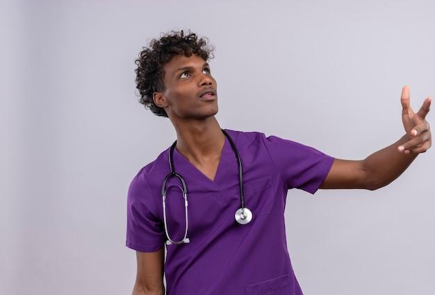 Pewny Siebie Młody Przystojny Ciemnoskóry Lekarz Z Kręconymi Włosami W Fioletowym Mundurze Ze Stetoskopem Patrzącym W Górę Podczas Podnoszenia Rąk Darmowe Zdjęcia