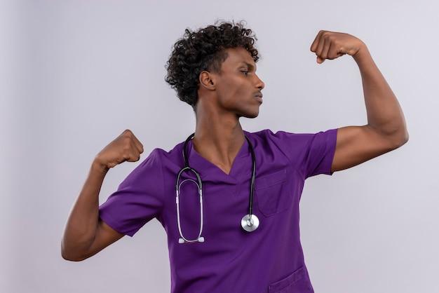 Pewny Siebie Młody Przystojny Ciemnoskóry Lekarz Z Kręconymi Włosami W Fioletowym Mundurze Ze Stetoskopem Pokazującym Gest Siły Darmowe Zdjęcia