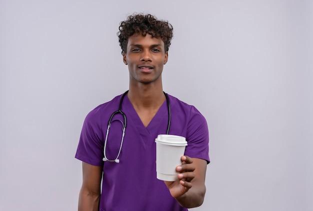 Pewny Siebie Młody Przystojny Ciemnoskóry Lekarz Z Kręconymi Włosami W Fioletowym Mundurze Ze Stetoskopem Przedstawiającym Papierowy Kubek Z Kawą Darmowe Zdjęcia