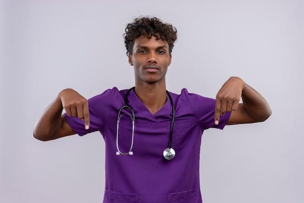 Pewny Siebie Młody Przystojny Ciemnoskóry Lekarz Z Kręconymi Włosami W Fioletowym Mundurze Ze Stetoskopem Skierowanym W Górę Palcami Wskazującymi Darmowe Zdjęcia