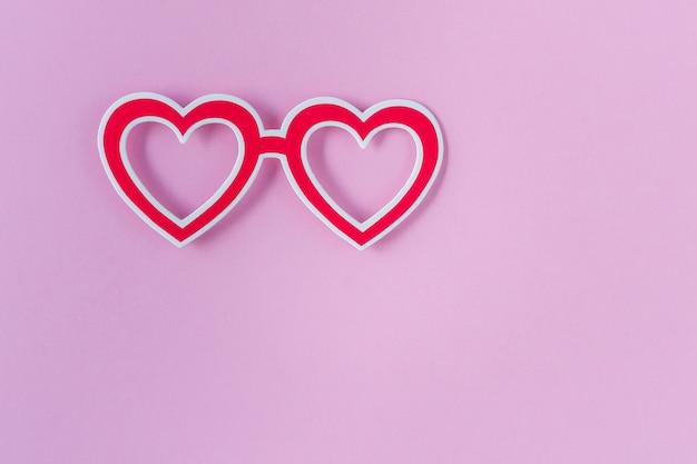 Photo Budka Podpiera Okulary Na Różowym Tle. Czerwone Okulary W Kształcie Serca. Zestaw Na Walentynki, Urodziny Lub Imprezę. Widok Z Góry. Leżał Płasko. Skopiuj Miejsce Premium Zdjęcia