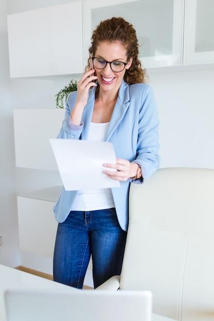 Piękny młody bizneswoman używa jej telefon komórkowego w biurze. Darmowe Zdjęcia