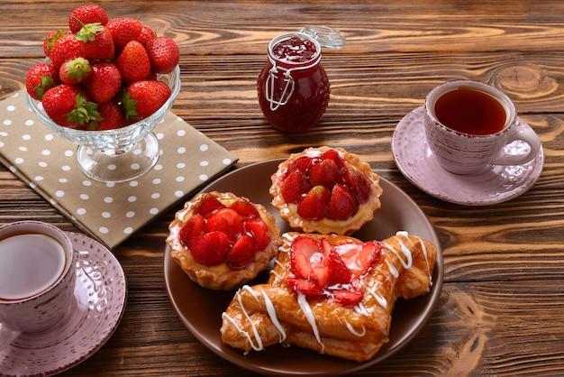 Picie Herbaty Z Tartaletkami I Ciastka Z Truskawkami Premium Zdjęcia