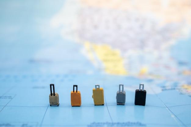 Pięć miniaturowych figur bagażu z wieloma stylami stoi na mapie świata. Premium Zdjęcia