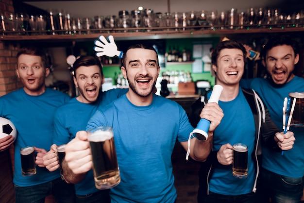 Pięciu Fanów Sportu Pijących Piwo W Barze Sportowym Premium Zdjęcia