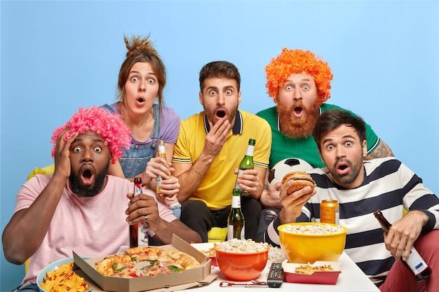 Pięciu Różnych Przyjaciół Wpatruje Się W Telewizor Z Szokiem Darmowe Zdjęcia