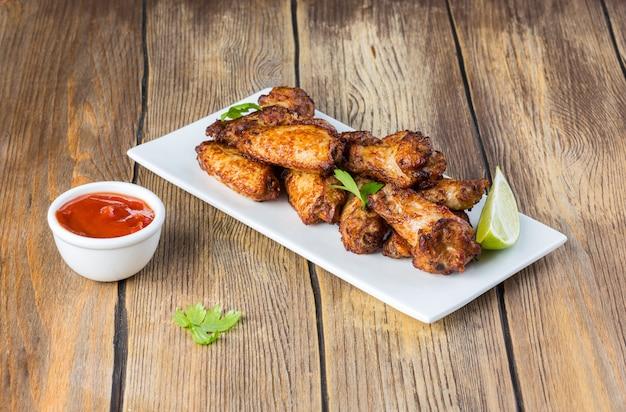 Pieczone Skrzydełka Kurczaka Z Limonką I Sosem Pomidorowym Premium Zdjęcia