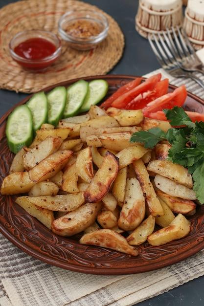 Pieczone Ziemniaki Podawane Z Pomidorami, Ogórkami I Natką Pietruszki Na Talerzu Na Ciemnym Tle Premium Zdjęcia
