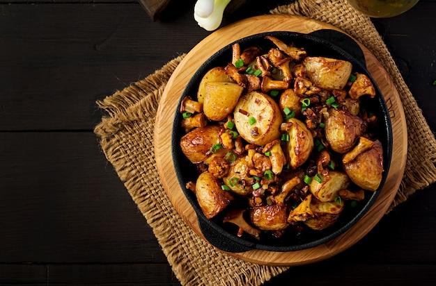 Pieczone Ziemniaki Z Czosnkiem, Ziołami I Smażonymi Kurkami Na Patelni żeliwnej Premium Zdjęcia