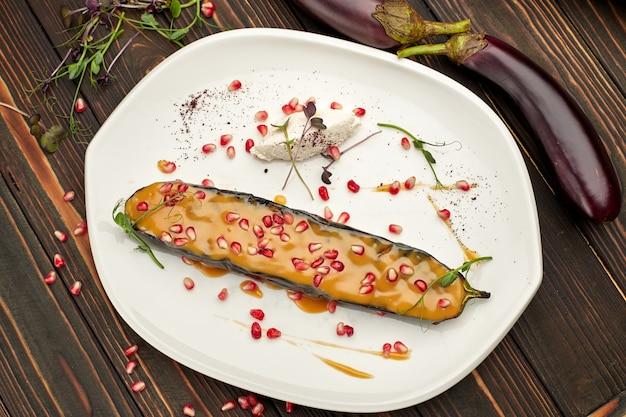 Pieczony Bakłażan Z Serem I Pestkami Granatu, Na Białym Talerzu, Na Drewnianym Stole Premium Zdjęcia