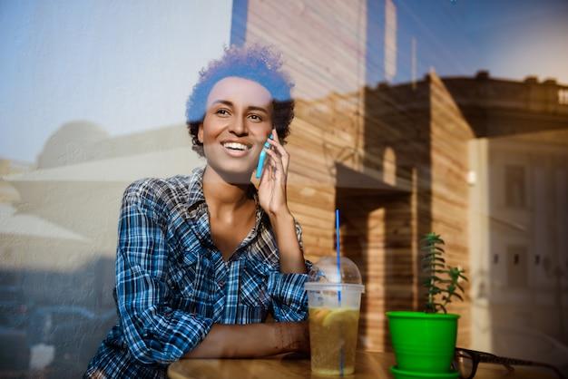 Piękna Afrykańska Dziewczyna Uśmiecha Się, Mówiąc Na Telefon, Siedząc W Kawiarni. Strzał Z Zewnątrz. Darmowe Zdjęcia