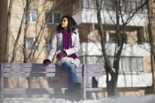 Piękna Amerykańska Czarna Kobieta W Ulicznym Zimy Obsiadaniu Na ławce Darmowe Zdjęcia