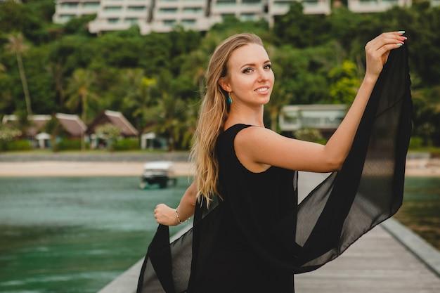 Piękna Atrakcyjna Kobieta Ubrana W Czarną Sukienkę Pozowanie Na Molo W Luksusowym Hotelu, Wakacje, Tropikalna Plaża Darmowe Zdjęcia