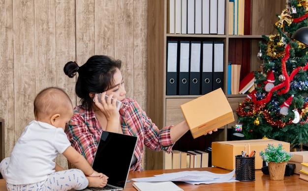 Piękna Azjata Matka Z Dzieckiem Pracuje W Domu Używać Laptop Blisko Choinki Premium Zdjęcia