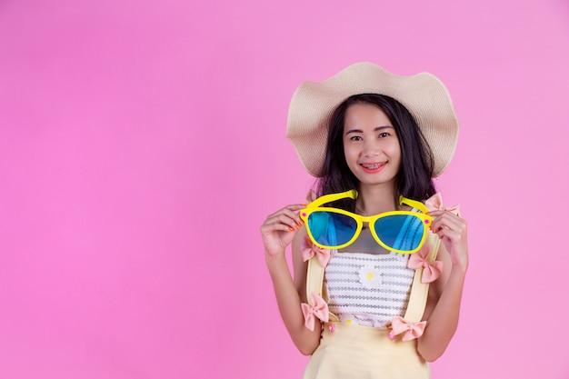 Piękna azjatycka kobieta jest ubranym kapelusz i duże szkła z menchiami. Darmowe Zdjęcia