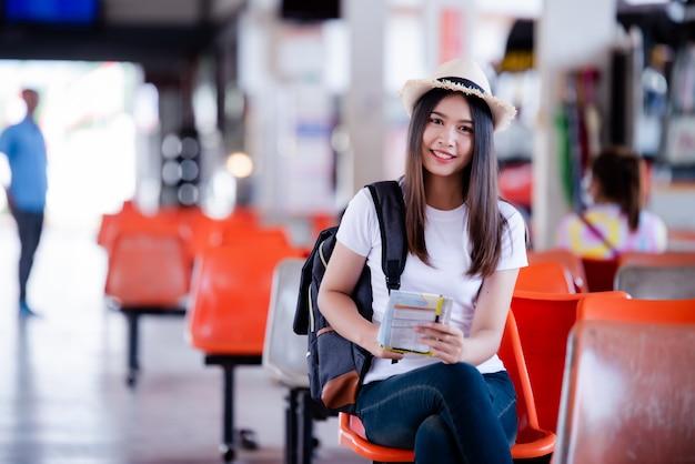 Piękna azjatycka kobieta ono uśmiecha się z mapą i torbą przy dworcem autobusowym Darmowe Zdjęcia