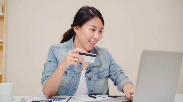 Piękna azjatycka kobieta używa laptop kupuje online zakupy kredytową kartą podczas gdy jest ubranym przypadkowego obsiadanie na biurku w żywym pokoju w domu. Darmowe Zdjęcia