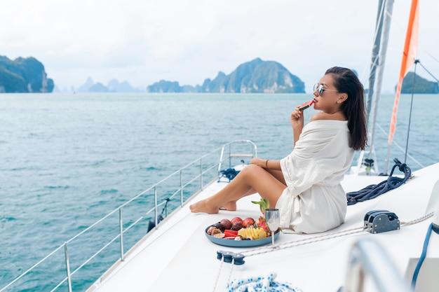 Piękna Azjatykcia Dama W Białym Szlafroku Na Jachcie Pije Szampana I Je Owoce, Morze Premium Zdjęcia