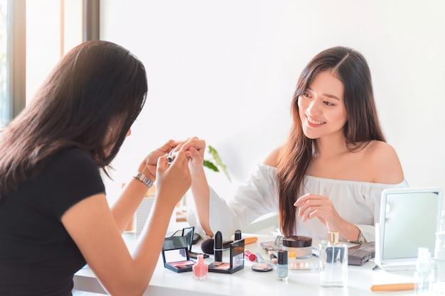 Piękna Azjatykcia Kobieta Blogger Pokazuje Jak Gwoździa Połysk I Używa Kosmetyka. Premium Zdjęcia