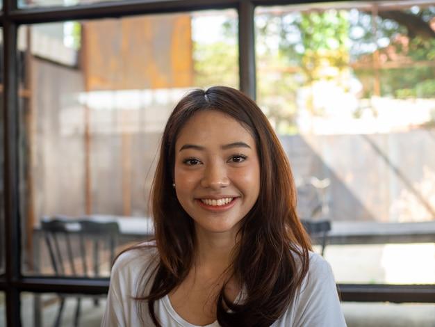 Piękna Azjatykcia Kobieta Ono Uśmiecha Się W Sklep Z Kawą Premium Zdjęcia