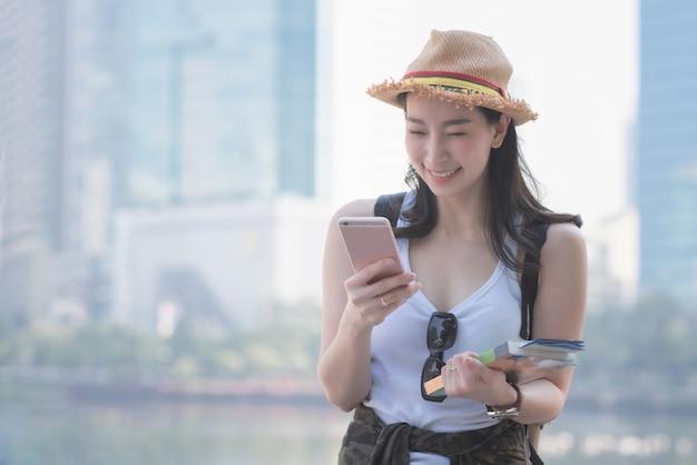 Piękna azjatykcia solo turystyczna kobieta uśmiechnięta i patrzeje telefon komórkowego Premium Zdjęcia