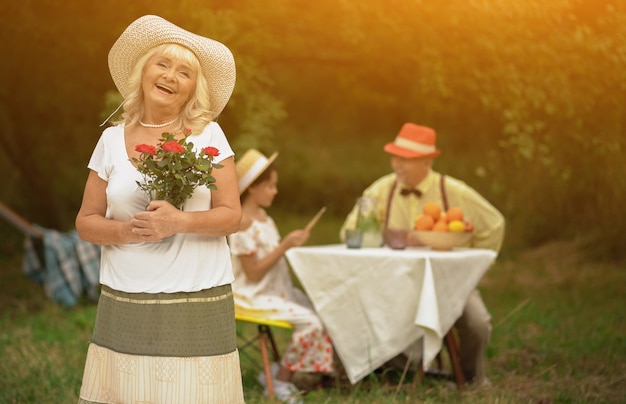 Piękna Babcia Z Bukietem Czerwonych Róż W Dłoniach Premium Zdjęcia