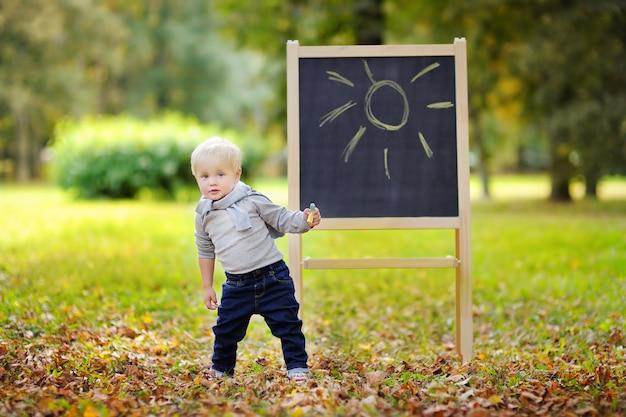Piękna Berbeć Chłopiec Rysunkowa Pozycja Blackboard Outdoors Premium Zdjęcia