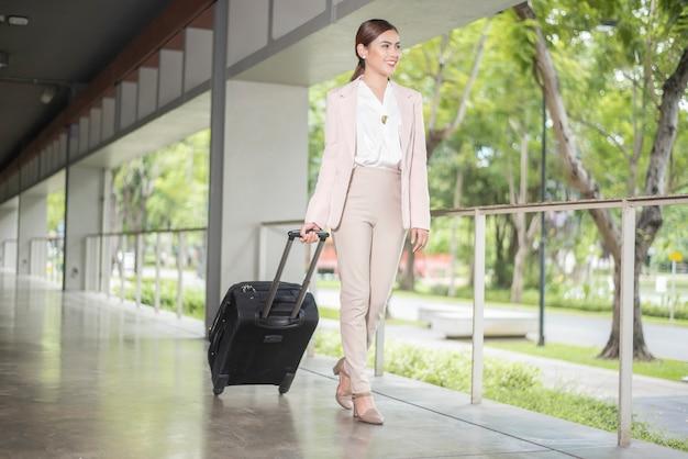 Piękna biznesowa kobieta chodzi w lotnisku, biznesowej podróży pojęcie Premium Zdjęcia