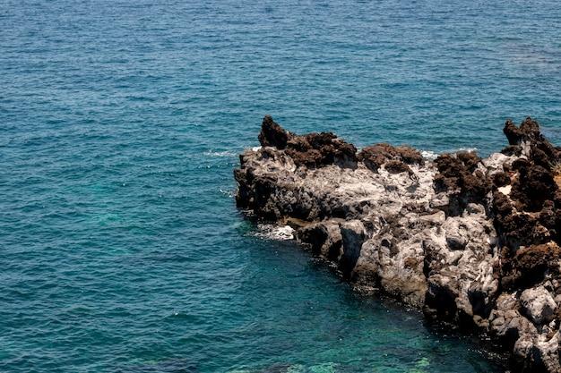 Piękna błękitna woda morska z skałami Darmowe Zdjęcia