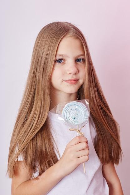 Piękna blond dziewczyna zjada karmel lollipop Premium Zdjęcia