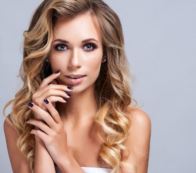 Piękna Blond Kobieta Z Długim Kędzierzawym Włosy Premium Zdjęcia