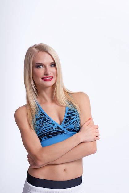 Piękna Blondynka Fitness Kobieta Uśmiechając Się Z Rękami Skrzyżowanymi, Pozowanie Pewnie Darmowe Zdjęcia