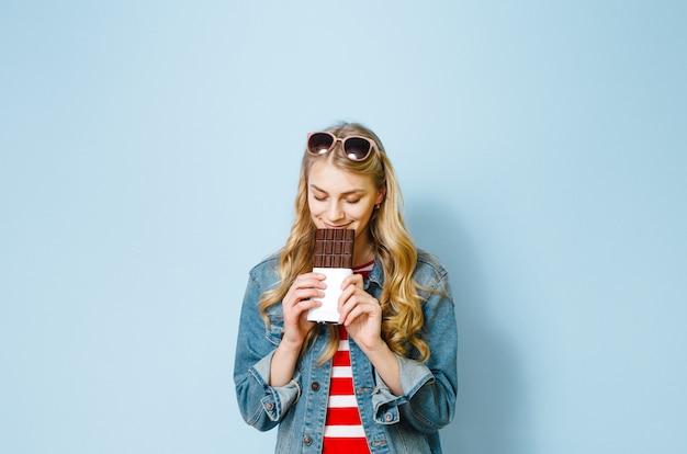 Piękna Blondynka Jedzenia Czekolady Jest Podekscytowana Na Niebieskim Tle Premium Zdjęcia
